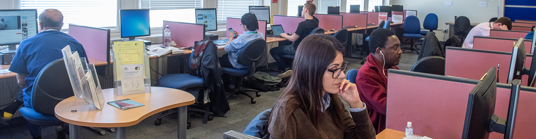 Students sit at individual desks each using a desktop computer, they are separated with red separators