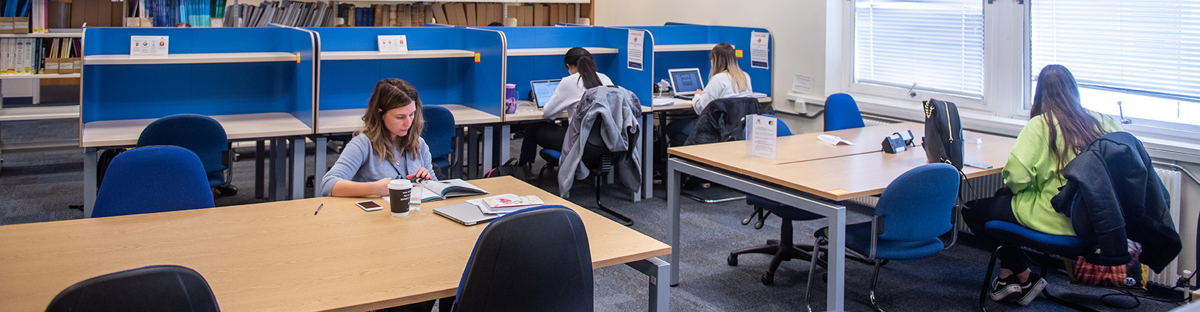 Tables in a room - some have blue separators - students are dotted about working at the desks