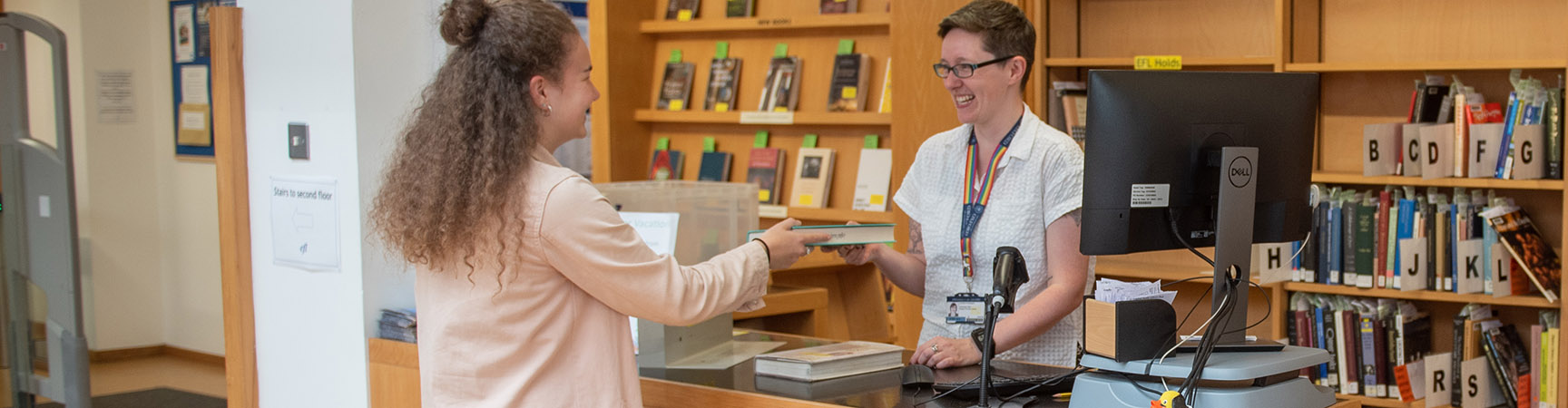 A student handing a book to a librarian at the information desk
