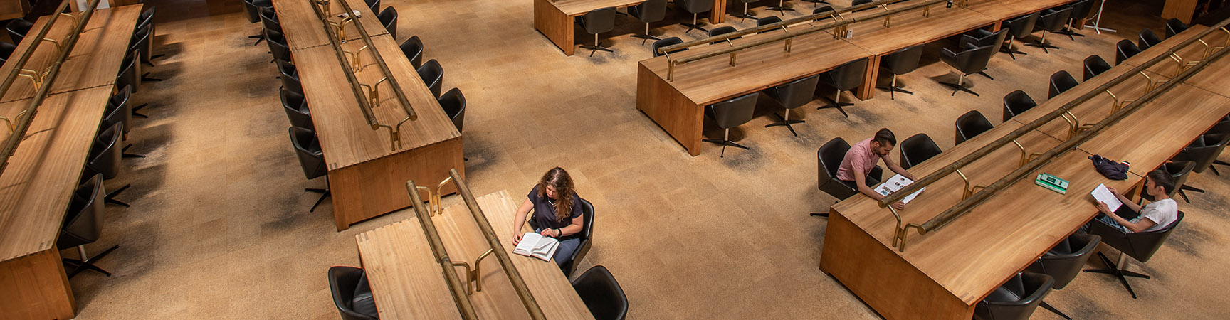 A birdseye view six long wooden desks, four students are scattered around reading at them