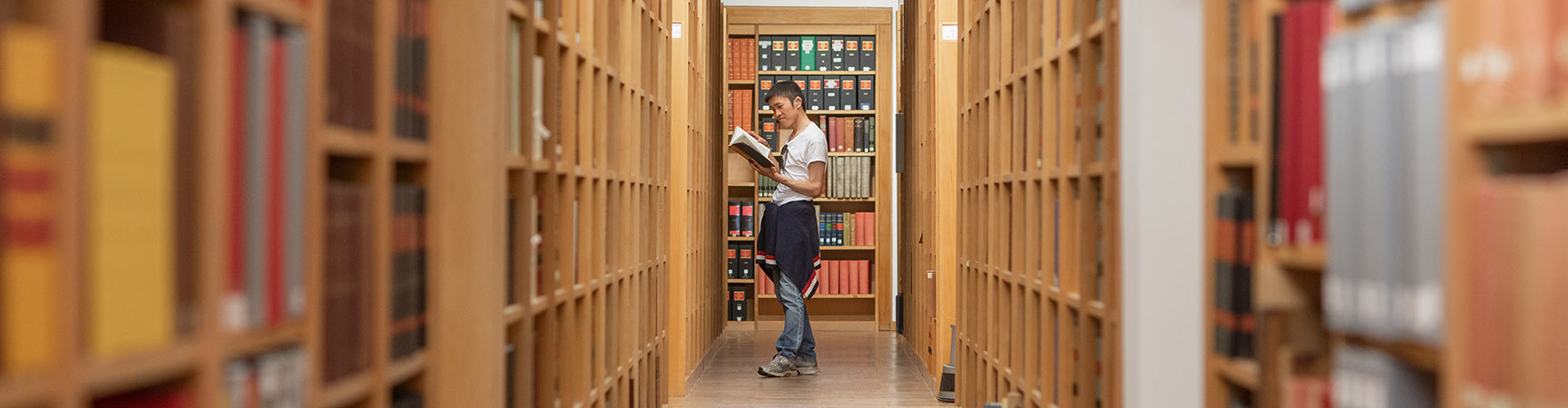 A long row of wooden bookshelves either side of a walkway, a student stands at the end reading