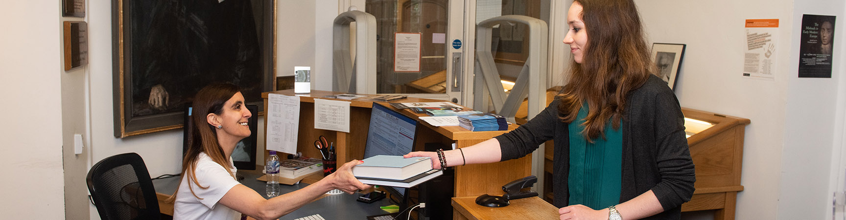 A librarian hands over a book to a student