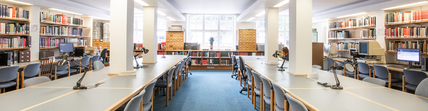 Two rows of desks with bookshelves on each side