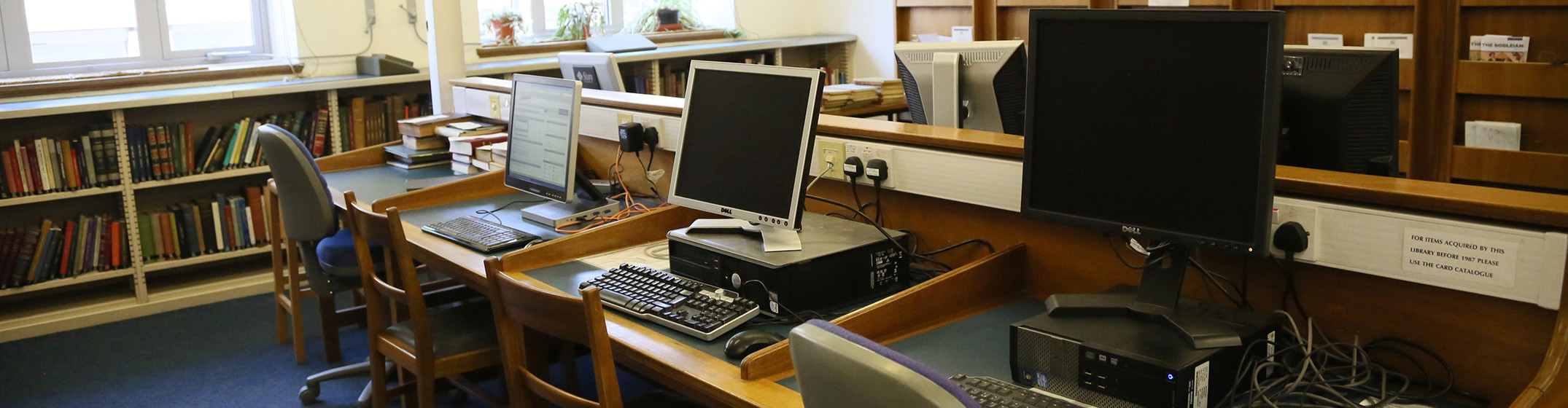 A row of three desktop computers on a wooden desk