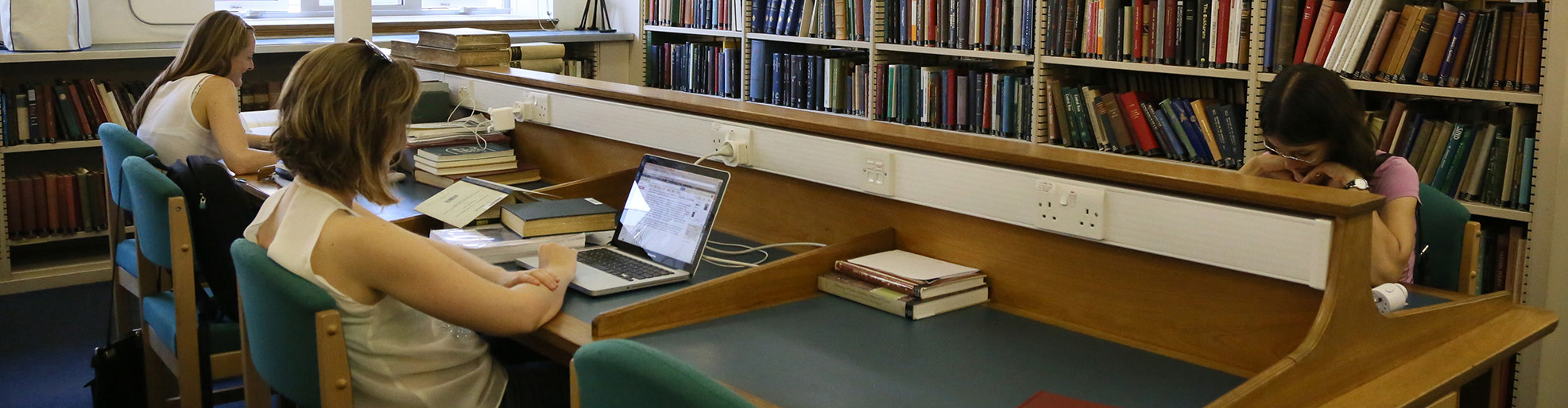 Two students sit next to each other at a three-seater library desk