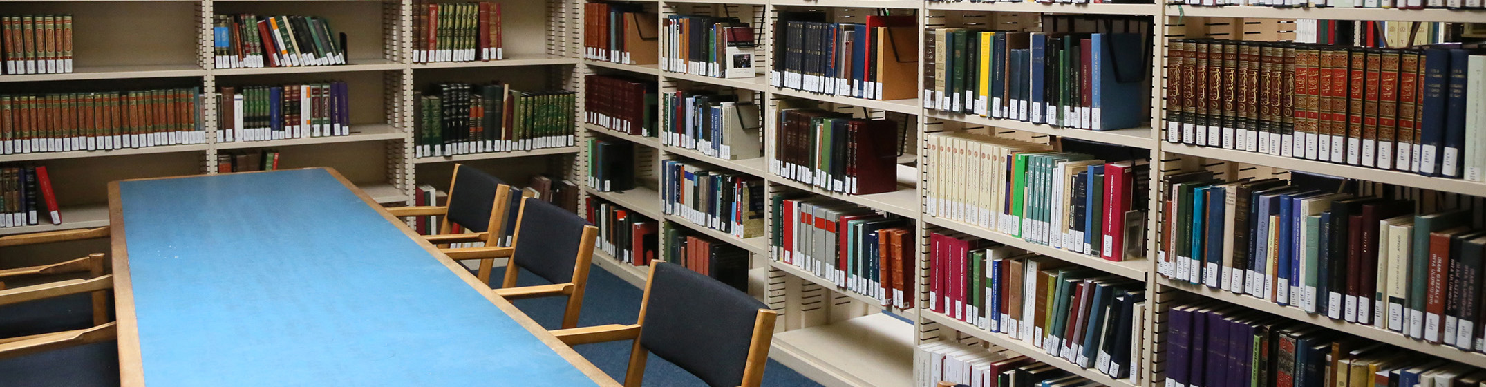 A long blue table surrounded by bookshelves