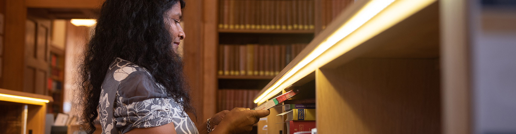 A student retrieves a book from a shelve