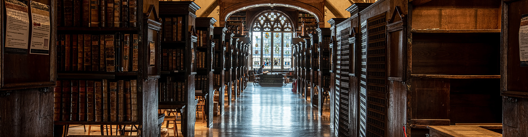 A long room with a stained glass window at the end, there are wooden book shelves and alcoves on either site
