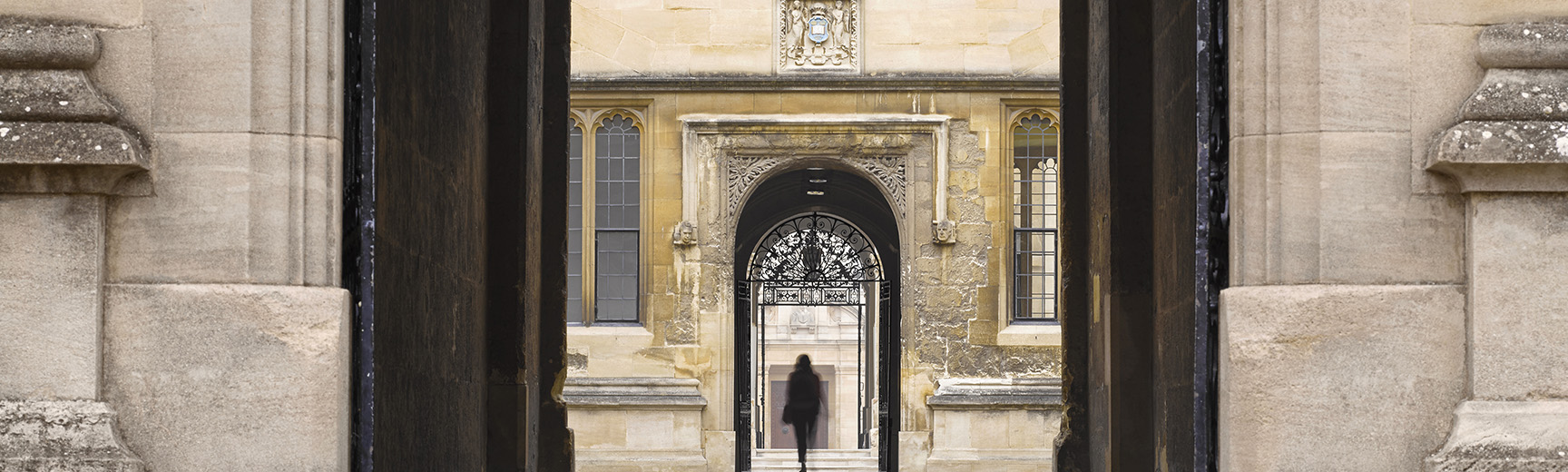 The silhouette of a person walking through an archway into the Old Bodleian Library