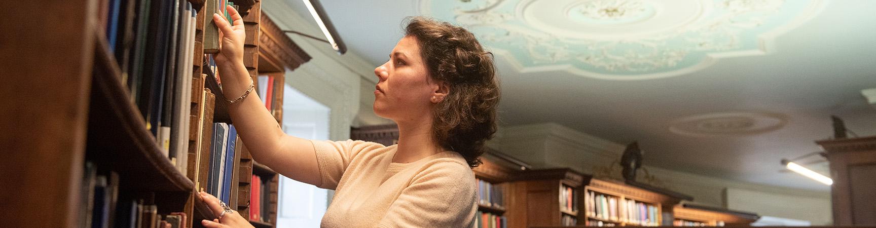 A student pulls a book off a bookshelf