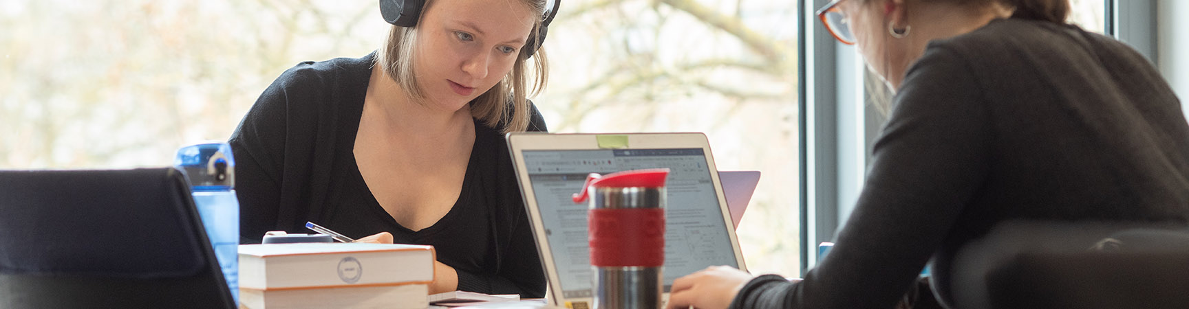 Two students work opposite each other at a desk. One has a KeepCup