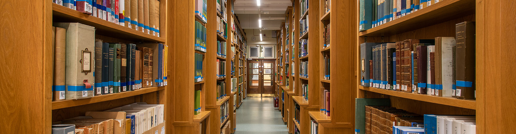 Two rows of bookshelves on either side of a walkway