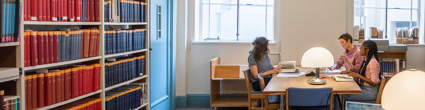 Three students sit around a wooden desk. They are in conversation. There is a bookshelf on one side of the room and large windows on another