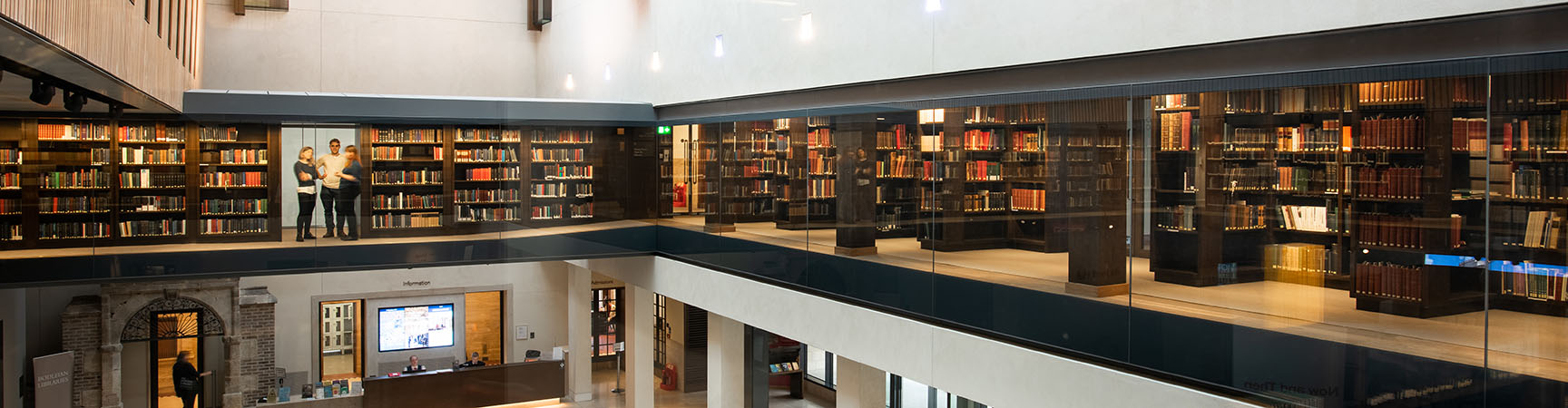 A two-storey height room with a glass mezzanine filled with bookshelves