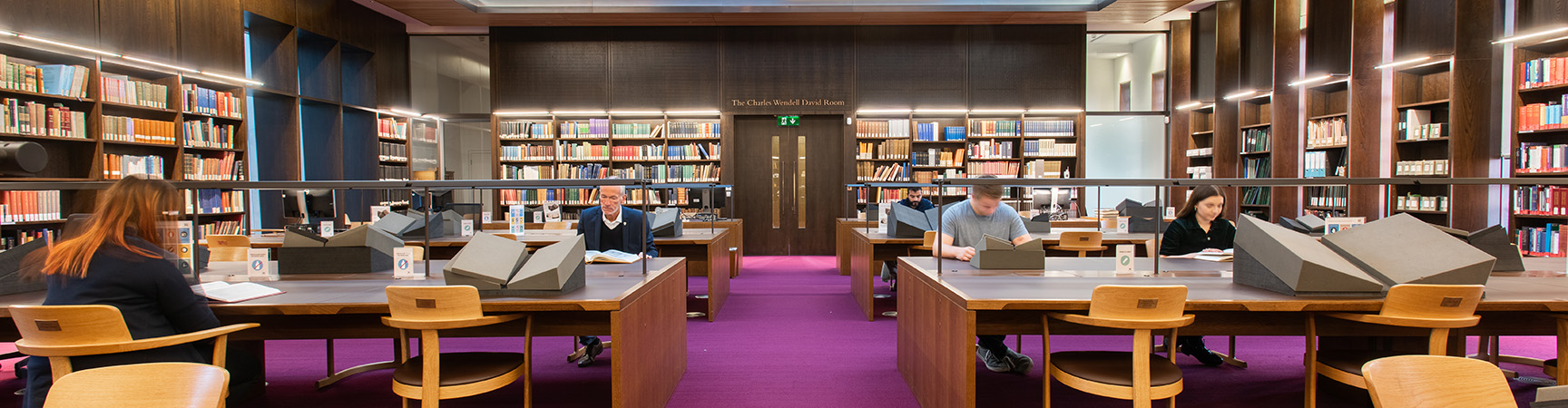 Two large desks with readers either side on a purple carpet