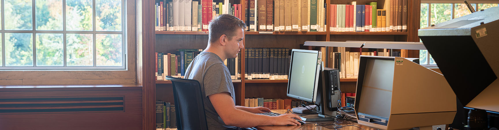 A student sitting at a desk in front of a microfiche reader