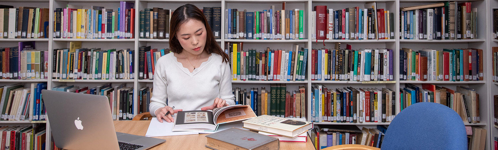 A student sits at a table - they look at a book and have an open laptop - behind is a bookshelf covering the whole wall