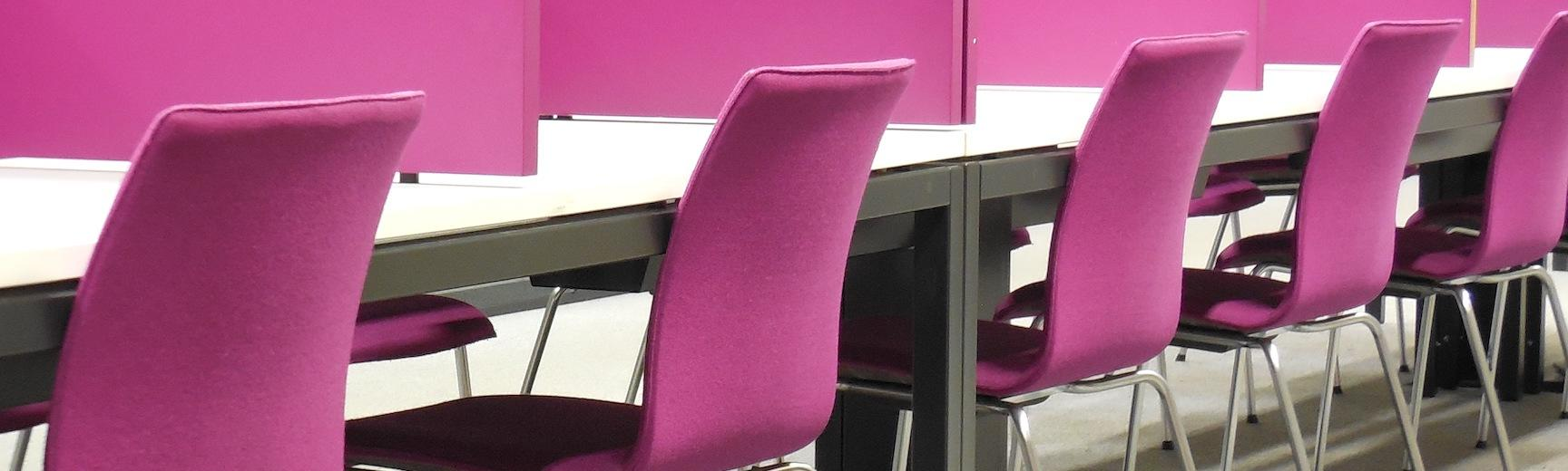 Pink chairs at tables separated by dividers