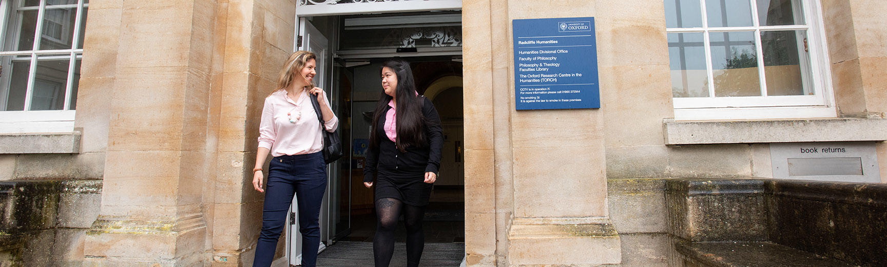 Two students leave a beige stone building