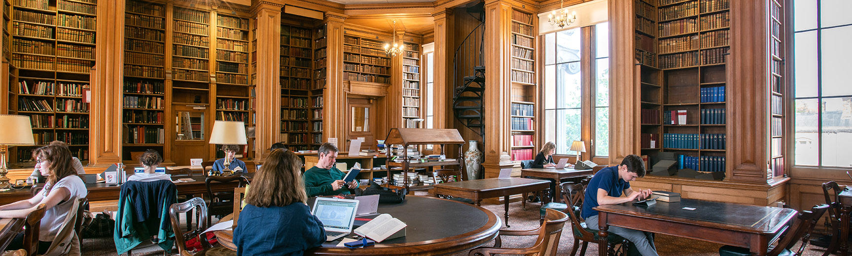 Students sit at individual desks in a wood-panelled room with bookselves