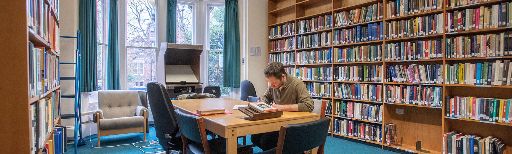 A student working at a desk in the middle of a room surrounded by bookshelves
