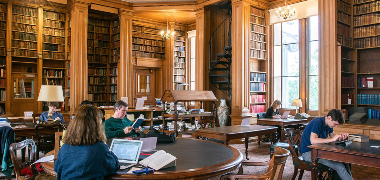 Students sit at individual desks in a wood-panelled room with bookshelves