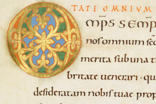 An illuminated manuscript in Latin with an 'O' painted in gold leaf