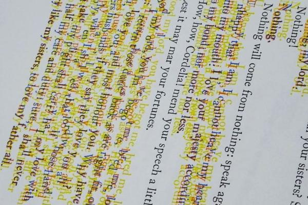 A slanted view of a page of printed type with some lines blurred and outlined in yellow