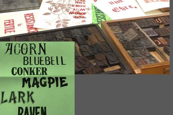 An image of wood type blocks and prints in red ink