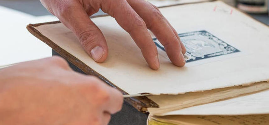 A pair of hands repairing the page of a rare book