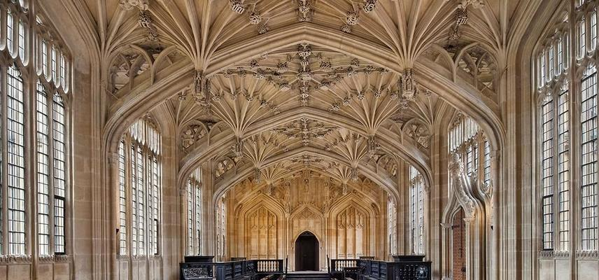 The inside of Divinity School - pale stone makes up the walls and ornately decorated ceiling, there are windows down each side and at the far end a small arched wooden door