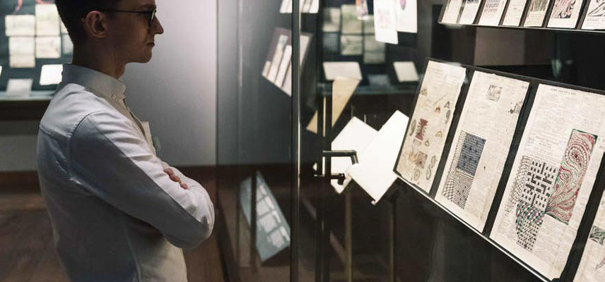 A view of an exhibition: a person looks at a glass display case - with 2D material within it