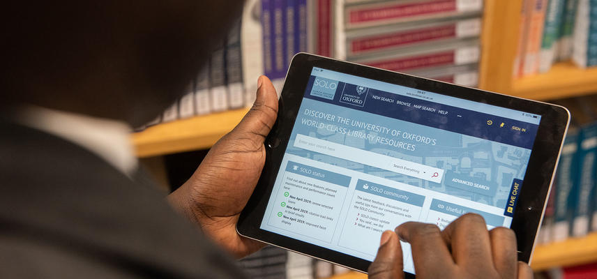 A library reader holds a tablet device in their hands, on it they are using the SOLO website - our online resource discovery tool