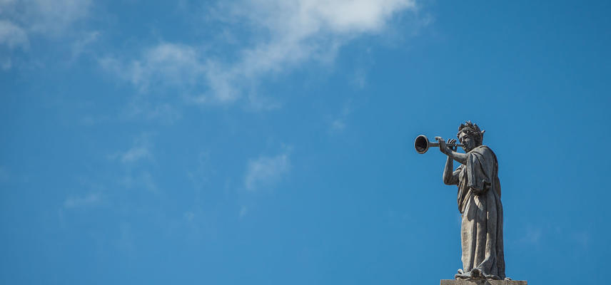 A statue of a person blowing a trumpet against a bright blue sky background