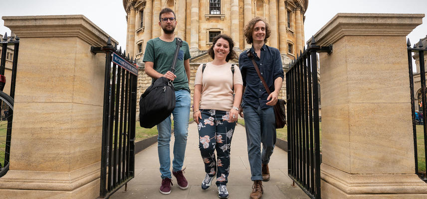 Three students walk towards the camera up the path away from the Radcliffe Camera Library