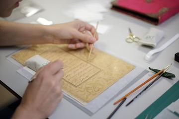 A detail of a person's hands over a manuscript document. They hold a wooden tool in each hand and delicately work on the document
