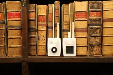 Two small white plastic monitors - for temperature and humidity - sit on a bookshelf in front of some rare books