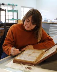 A woman holds what looks like a pair of tweezers and moves them towards a historic book - in front of the book are two petri dishes