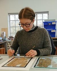 A woman sits at a desk - she has a paint brush in each hand and is working on a fragile manuscript that is broken into many pieces