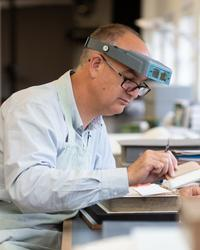 A side profile of a man - he has microscope glasses on his head - he holds a brush in his hand and works on a historic book