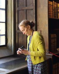 A woman stands in an old part of the library - the walls are panelled with wood - and she is looking at a piece of monitoring equipment in her hands