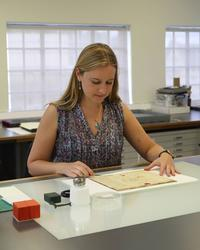 A woman stands next to a desk, she has a manuscript in front of her - to the left are glass bottles and other conservation equipment