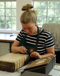 A woman sits at a desk wearing an apron. In front of her is a large book with its cover off - she is using an implement to conserve the spine of the book