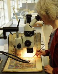 A woman looks through a microscope, beneath the microscope is an open book. The woman is using a paint brush to carry out conservation work on it.