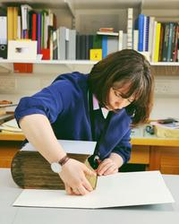 A woman leans over a large old book - she is wrapping it in a protective cover