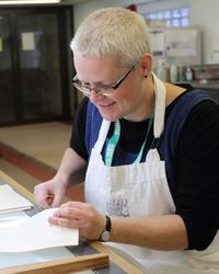 A woman wears a white apron, in her hands she is holding a piece of paper that she is sewing