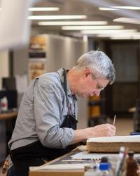 A side profile of a man - he is sitting down at a desk looking down, a book is open in front of him and he works on it with a small implement
